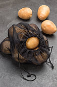 Potatoes in black reusable bag. Potatoes on table.