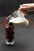 Hand pours milk from measuring cup into glass with coffee ice cubes