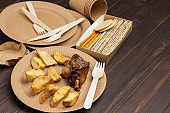 Fried potatoes and chicken in Eco-friendly cardboard disposable dishes.