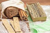 Crispbread on plastic bag. Bread and straws in linen bag.