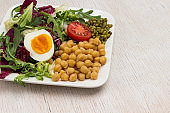 Chickpeas, mung bean, egg and greens in white background.