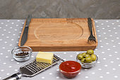 Homemade food. Serving board knife and fork, olives cheese grater