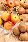 Potatoes and apples in wooden dishes and plastic bags.