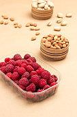 Raspberries in plastic container. Almonds in wooden box.