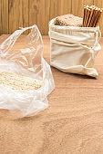 Crispbread in plastic bag. Bread and straws in linen bag.