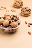 Walnuts in plastic container. Almonds in wooden box.