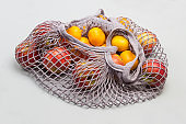 Hand holds string bag mesh with red apples and tangerines.