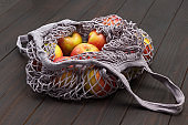 Red apple in reusable cotton mesh bag.