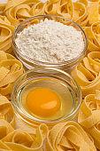 Wheat pasta, flour and raw egg on white background