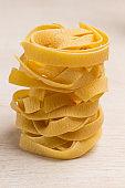 Raw wheat pasta on white background
