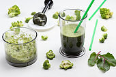 Mugs with green vegetable smoothies. Metal chopper on saucer