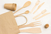 Wooden forks and knives in paper bag.