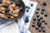 Blueberries and blackberries with pancakes in black bowl. Berries and napkin on table.