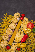 Uncooked pasta with vegetables tomatoes, yellow and red peppers