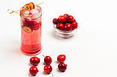 Homemade refreshing summer apple drink with ice in glass. Sliced apples on stick. Small red apples on table
