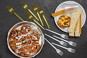 Raisin buns in baking dish. Bun and crispbreads in plastic disposable plate.