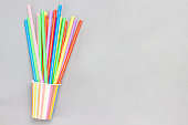 Colorful paper cups and colorful plastic straws for drinks.