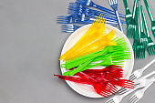 Colorful plastic forks on white plate. Disposable plastic tableware.