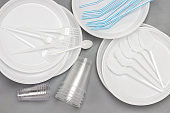Disposable white plastic tableware. Plate, spoons, forks, straws for drinks.