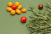 Cherry tomatoes and rosemary on green