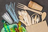 Wooden forks and knives in paper bag. Colored plastic forks, glasses, beverage straws in plastic bag