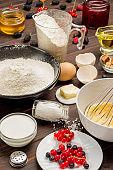 Ingredients for cooking breakfast. Flour berries, eggs whisk, honey jam, yogurt on table.