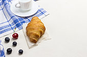 Croissant on white and blue checkered napkin. Blueberries on table