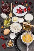Empty pan and whisk. Flour, broken eggs, berry milk, butter, honey jam.