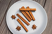 Cinnamon sticks and star anise in gray ceramic plate.