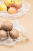 Potatoes and apples in plastic bags.