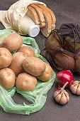 Potatoes in plastic bag. Bread and milk in linen bag.