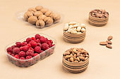 Raspberries and walnuts in plastic containers.