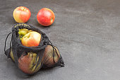 Apples in black reusable bag. Apples on table.
