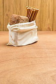 Bread and edible straw in linen bag.