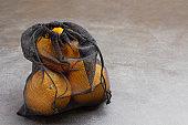 Oranges in black reusable bag. Ecological concept.