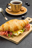 Croissant with jamon and cheese and greens.