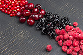 Blackberry, red currants, cherry, and raspberry on black background.
