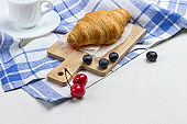 Croissant on white and blue checkered napkin. Cup of coffee cherry and blueberries