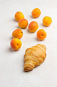 Croissant and apricots on white background