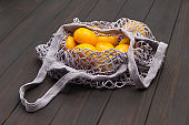 Hand holds string bag mesh with tangerines.