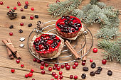 Berry muffins on metal tray. Cinnamon sticks, raisins and cranberries on table. Fir branches.