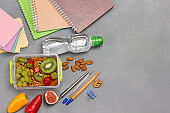 Lunchbox with nuts and fruits. Pens and notebooks, note paper. Bottle of water.