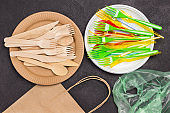 Wooden forks and knives on cardboard plate and  paper bag.