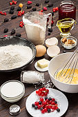 Ingredients for baking berry pie. Berries, flour in black plate. Measuring cup with flour, glass of milk, broken egg. Metal whisk in bowl.