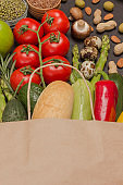 Healthy lifestyle concept. Paper bag with vegetables, nuts