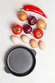 Frying pan. A set of vegetables for a healthy diet, eggs, red peppers, tomatoes, onions, garlic