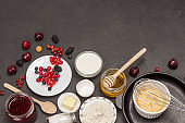Bowl with beaten eggs, metal whisk in frying pan. Berries, flour in plate. Berries, flour in plate.