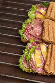 Grilled sandwich with salami, cheese tomatoes and greens on metal grill
