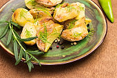 Fried potatoes with dill and rosemary on a green ceramic plate