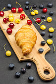 Croissant on cutting board. Blueberries, red and yellow cherries on table.